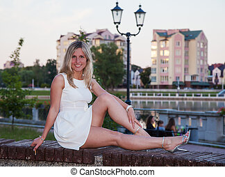 young beautiful woman in white dress sitting on a park bench