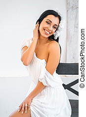 young beautiful woman in white dress sitting on chair