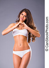 Young beautiful  woman in white fitness clothing