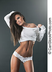 Young beautiful woman in white lingerie in studio