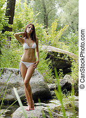 Young beautiful woman in wild forest