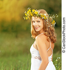 young beautiful woman in wreath of flowers lies in the green grass outdoors in nature