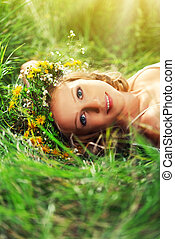 young beautiful woman in wreath of flowers lies in the green...
