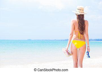 young beautiful woman in yellow bikini and straw sun hat...