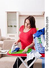 Young beautiful woman ironing at home