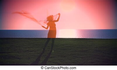 Young beautiful Woman is dancing on the sea at sunrise. Reverse.