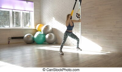 Young beautiful woman is doing exercises in a fitness room.