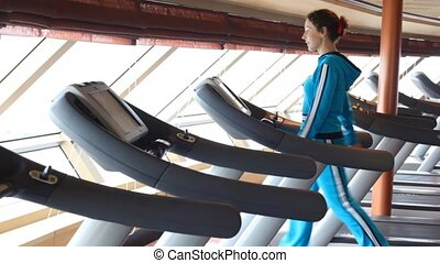 woman is exercising in gym - young beautiful woman is...
