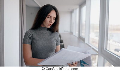 Young beautiful woman is looking at project standing in modern office.