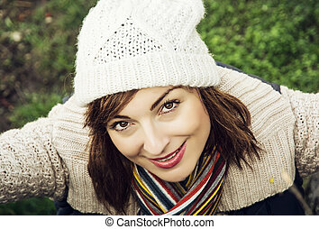 Young beautiful woman is posing in autumn outdoor outfit