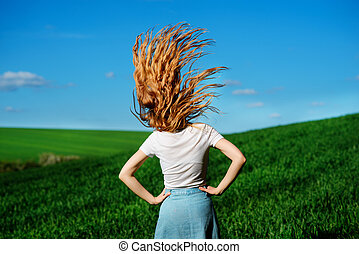 Young beautiful woman is shaking her hair on greenfield from...