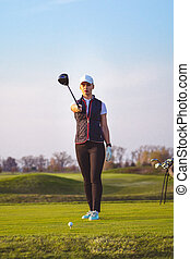 Young beautiful woman is training golf