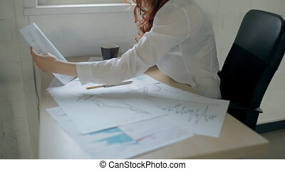 Young beautiful woman is working with paper project sitting at office desk.
