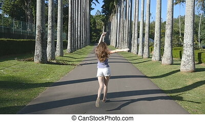 Young beautiful woman jogging and spinning along exotic...