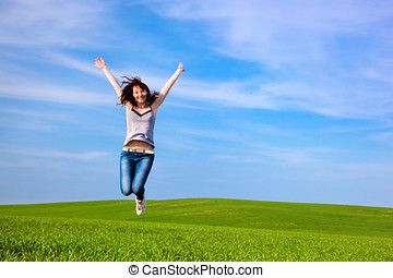 Young beautiful woman jumping for joy on green sunny field