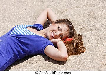 young beautiful woman laying on sand beach