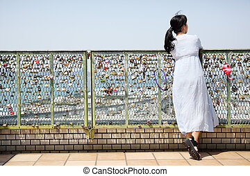 Young beautiful woman leans on fence