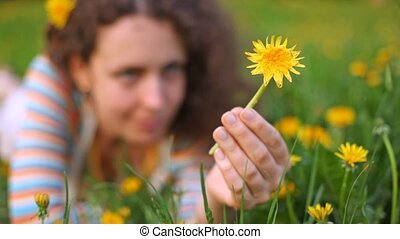 Young beautiful woman lies on lawn with dandelion in hand