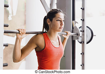 Young beautiful woman lifting weights in a gym