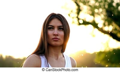 Young beautiful woman listening music at park while running. Portrait of smiling sporty girl with earphone looking at camera at park in autumn. Woman athlete looking at camera during winter sunset.