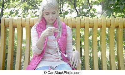 young beautiful woman listening music in the park