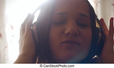 Young beautiful woman listening to music in headphones In sunlight at a sunny day.