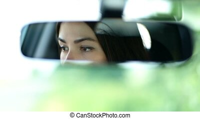 Young beautiful woman looking in rearview mirror - Young...