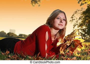 Young beautiful woman lying in a park with bouquet of yellow autumn leaves