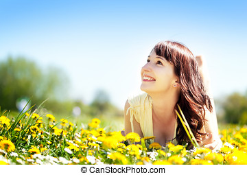 Young beautiful woman lying on grass full of spring flowers ...