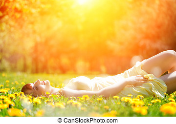 Young beautiful woman lying on grass full of spring flowers, relaxing
