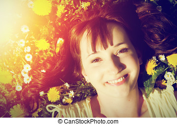 Young beautiful woman lying on grass full of spring flowers and smiling.