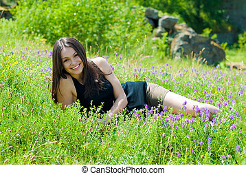 Young beautiful woman lying on green grass