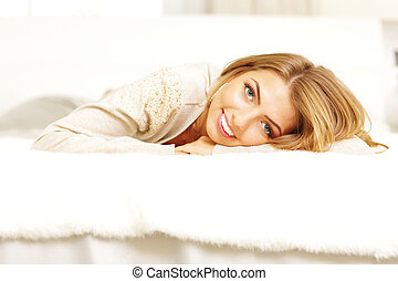 Young beautiful woman lying on the bed at home