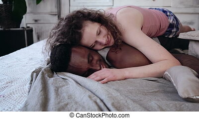 Young beautiful woman lying on the man in pajamas. Multiracial couple hugging on the bed, holding hands and smiling.