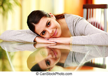 Young beautiful woman lying on the table at home