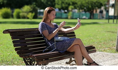 Young beautiful woman make selfy holding mobile phone in hand and sitting on the bench in the park
