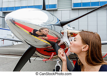 young beautiful woman make up face looking in reflection in a chrome fairing of a propeller of the business jet