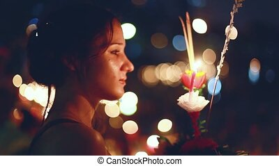 Young beautiful woman makes a wish in a carnival to celebrate the Loy Krathong Festival.