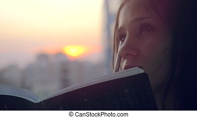 Woman making some important notes on notebook at sunset in the city. 4k