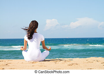 young beautiful woman meditation on beach