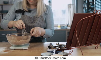 Young beautiful woman mixing ingredients in bowl, using...