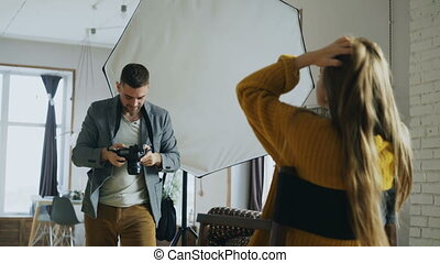 Young beautiful woman model posing for photographer man while he is shooting with a digital camera in photo studio indoors