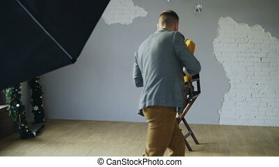 Young beautiful woman model posing for photographer while he is shooting with a digital camera in photo studio indoors