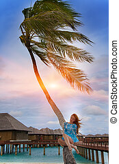 Young beautiful woman  near palm tree, Maldives