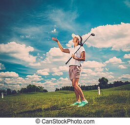 Young beautiful woman on a golf club field