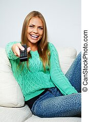 Young beautiful woman on a sofa with remote control