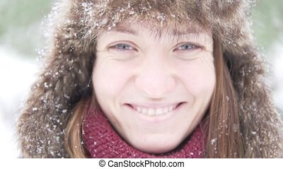 Young beautiful woman on a walk in the park in winter
