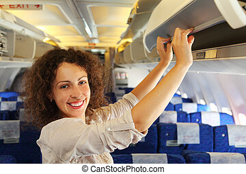 young beautiful woman on airplane adds baggage, rows of blue seats