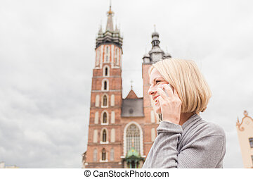 Young beautiful woman on the background of the St. Mary's Church in Krakow