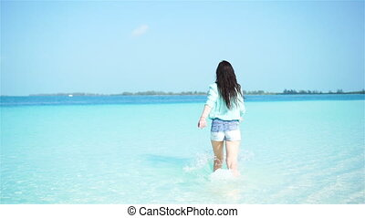 Young beautiful woman on the beach. Happy girl enjoy her tropical vacation exotic island